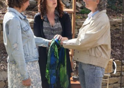 Wedding Celebrant officiates ceremony for two women. Outdoor casual wedding.