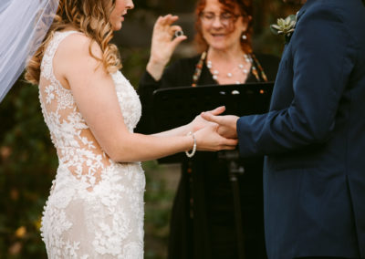 Wedding celebrant officiant presents the ring. Outdoor Asheville wedding. Bride and groom.